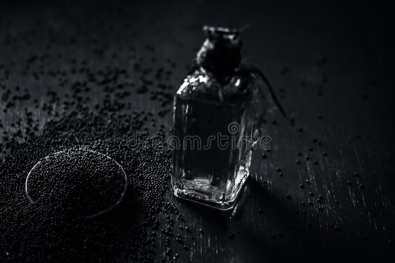 Close up of brown mustard seed,with its extracted oil on a brown wooden surface in dark Gothic colors.Its oil Boosts Cardiac Healt. H,Benefits the Skin,Treats stock photos