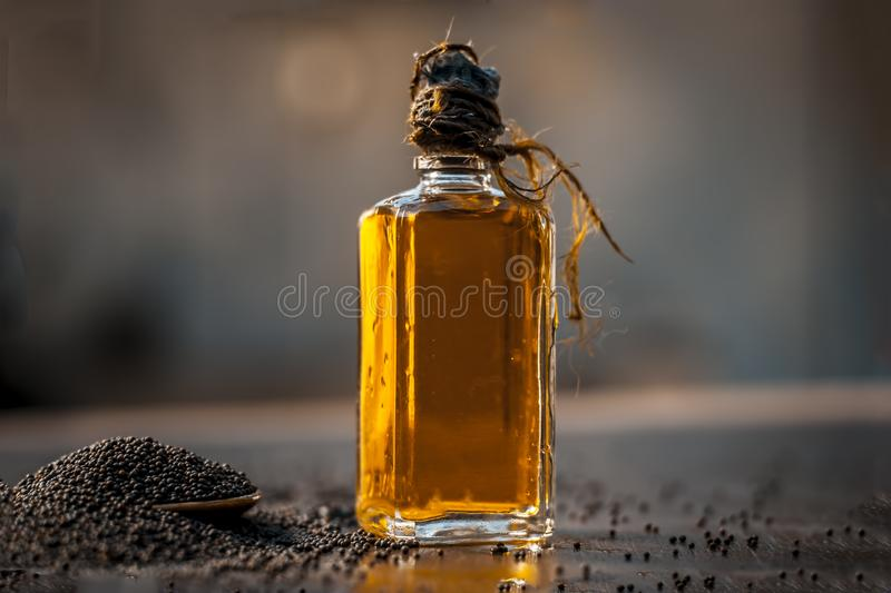 Close up of brown mustard seed,with its extracted oil on a brown wooden surface in dark Gothic colors.Its oil Boosts Cardiac Healt. H,Benefits the Skin,Treats royalty free stock image
