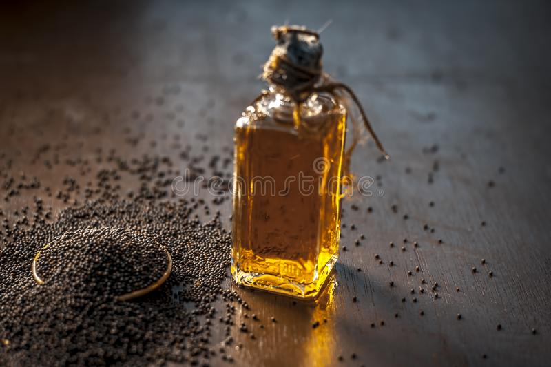 Close up of brown mustard seed,with its extracted oil on a brown wooden surface in dark Gothic colors.Its oil Boosts Cardiac Healt. H,Benefits the Skin,Treats stock photo