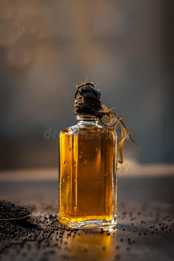 Close up of brown mustard seed,with its extracted oil on a brown wooden surface in dark Gothic colors.Its oil Boosts Cardiac Healt. H,Benefits the Skin,Treats stock images