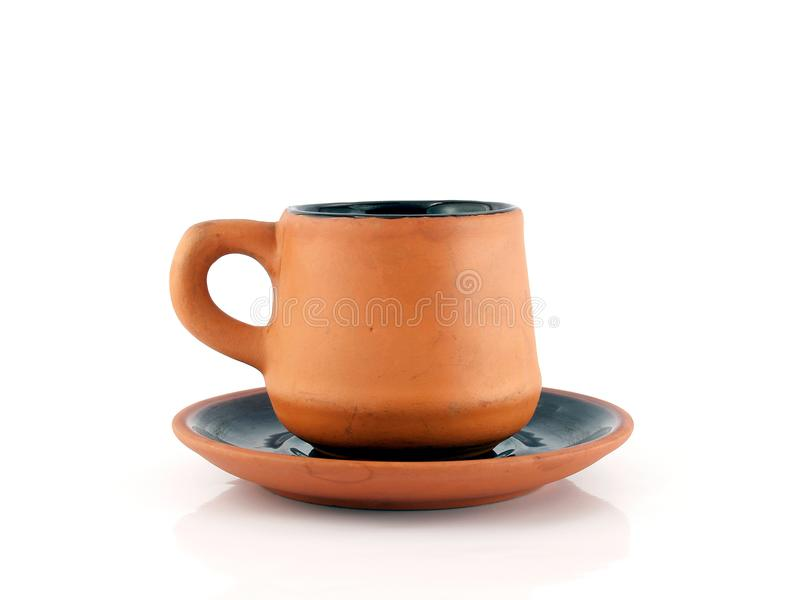 close up side of brown orange baked clay coffee cup with saucer isolated on white background royalty free stock image