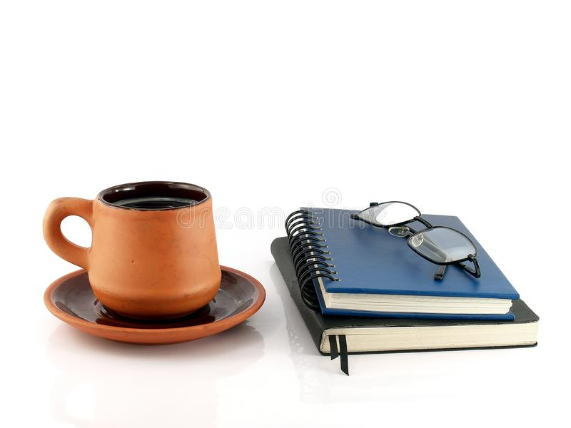 Close up brown orange pottery coffee cup with saucer and two closed diary books (blue and black) with eyeglasses. Brown orange pottery coffee cup with royalty free stock photography