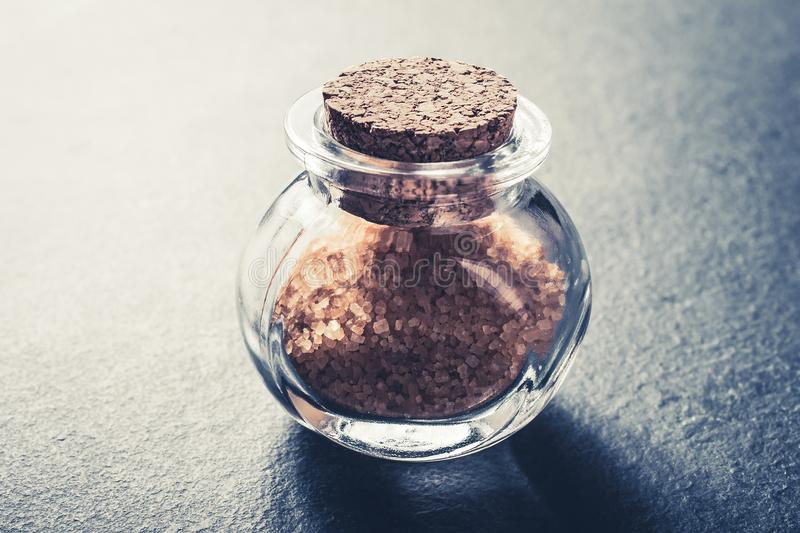 Close-Up Of A Brown Raw Sugar In A Small Glass Bottle Closed With A Cork Stopper On Slate Stone stock photos