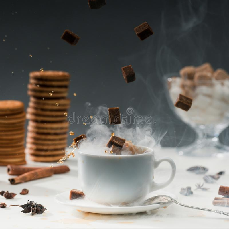 Close-up of brown sugar cubes falling into coffee cup. With splashes royalty free stock photos