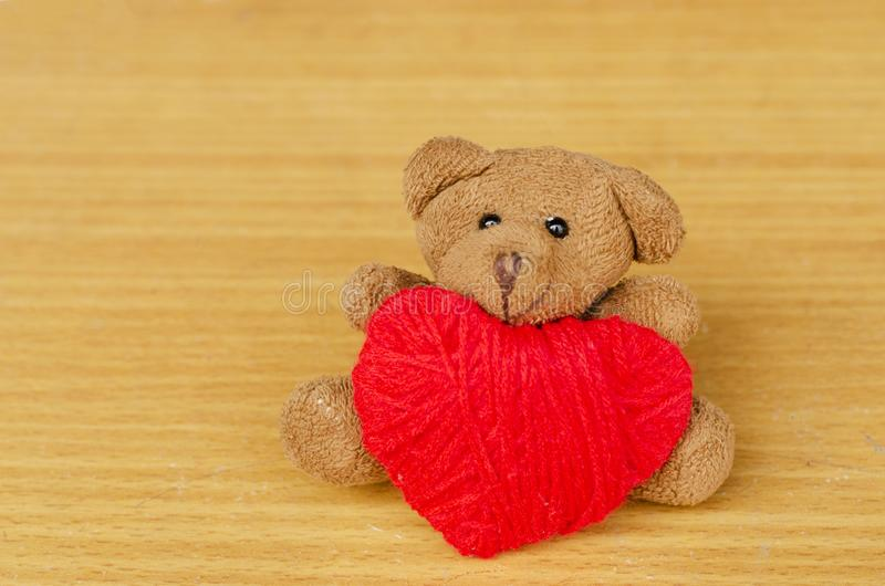 Brown teddy with red heart made from thread yarn for Valentines day concept. Close up of Brown teddy with red heart made from thread yarn for Valentines day stock images