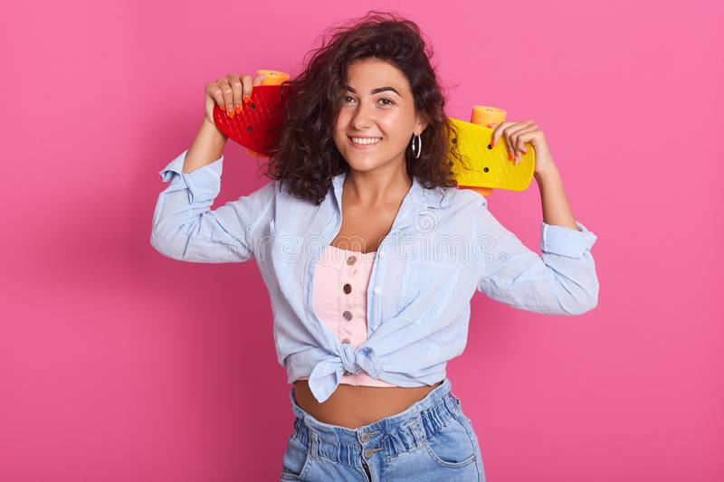 Close up of brunette charming woman with tender smile, holding skateboard on her shoulders, wearing t shirt, shirt and jeans,. Enjoys hobby,  over pink stock photos
