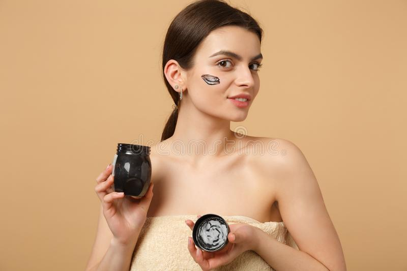 Close up brunette half naked woman 20s with perfect skin, nude make up black mask isolated on beige pastel wall. Background, studio portrait. Healthcare stock image