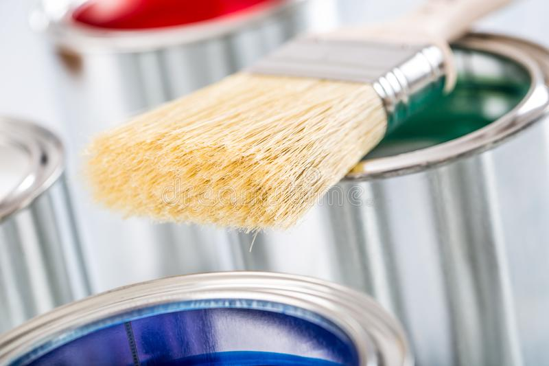 Close-up brush lying on multicolored paint cans stock photos