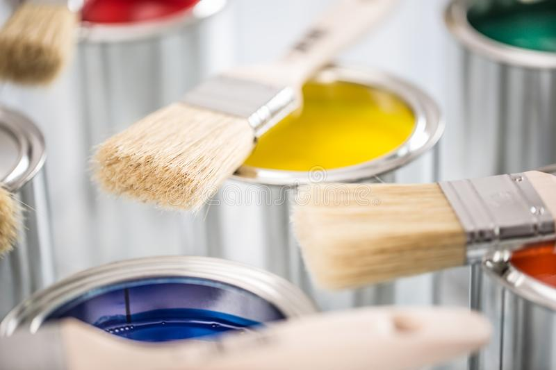 Close-up brushes lying on multicolored paint cans royalty free stock photography