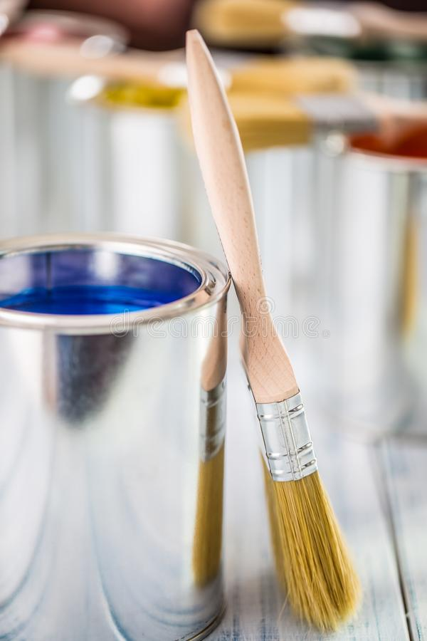 Close-up brushes lying on multicolored paint cans stock photo