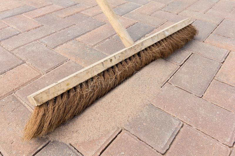 Brushing in kiln dried sand. Close up of brushing kiln dried sand in to joints of a block paved driveway stock images