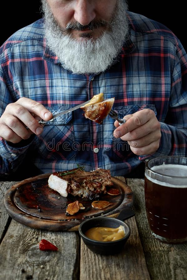 Close-up brutal gray-haired adult man with a beard eats mustard steak and drinks beer, concept of a holiday, festival, Oktoberfest. Close up brutal gray-haired royalty free stock photography