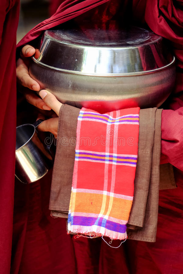 Close up of buddhist monk hands holding a bowl and cup stock image