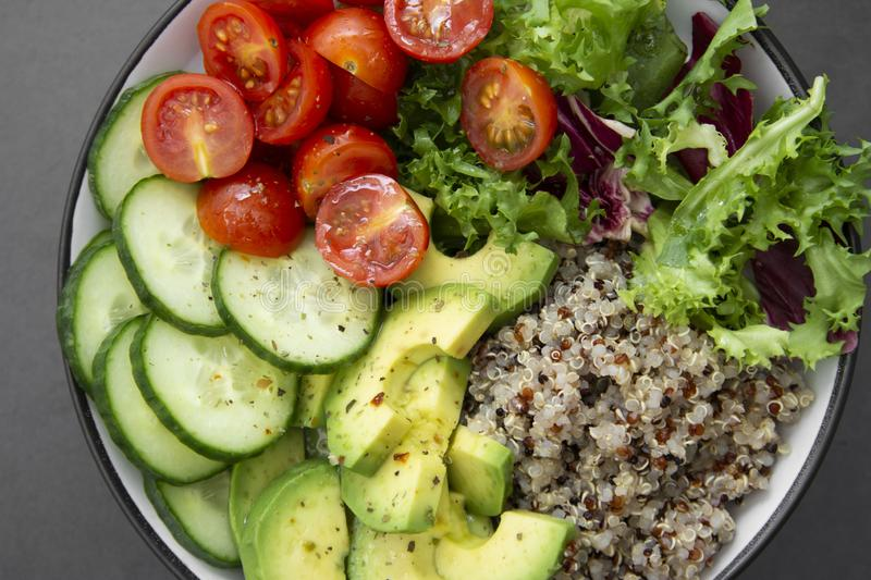Close up of budha bowl with quinoa, avocado, cucumber, salad, tomatoe, olive oil. Clean eating, diet food. Dark background. Close up of budha bowl with quinoa royalty free stock image