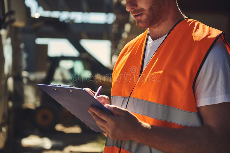 Close up of the builder making notes in his clipboard. Close up of professional builder in orange uniform standing outdoors and carefully making notes while stock photo