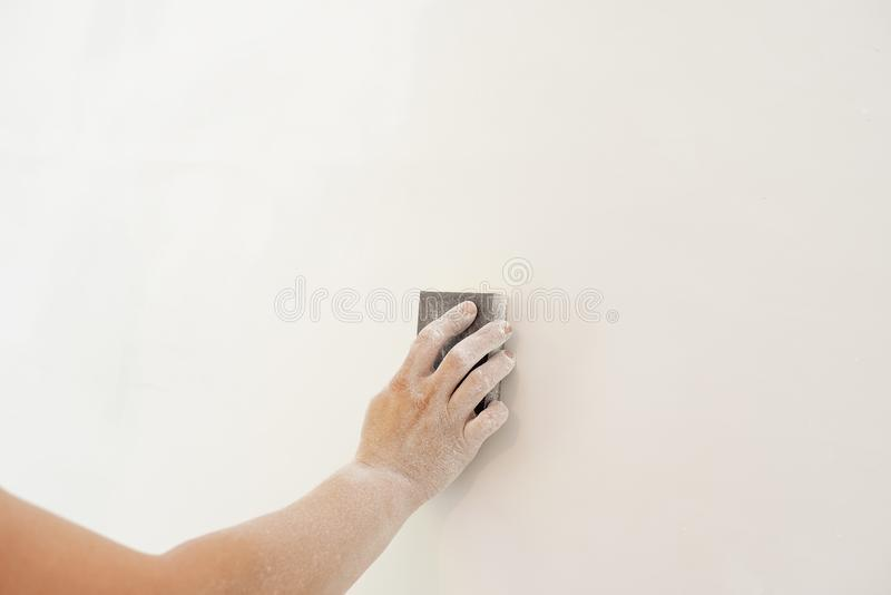 Close up of builder working with grinding tool. Repair and renovation at home. New interior design. Worker scrubbing the wall with royalty free stock photo