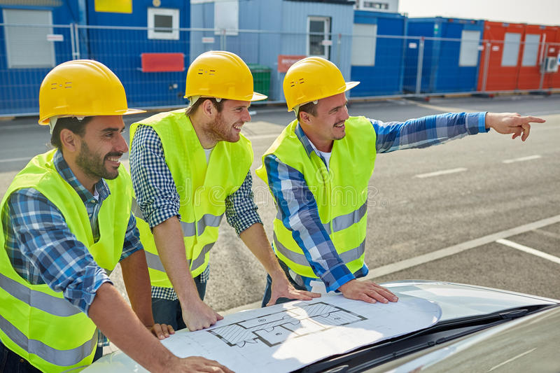 Close up of builders with blueprint on car hood. Building, construction, development, teamwork and people concept - close up of builders in hardhats and high royalty free stock images