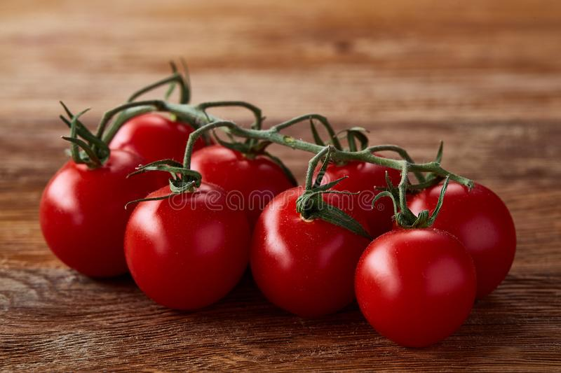 Close-up of a bunch of fresh cherry tomatoes on rustic wooden background, top view, shallow depth of field. stock images