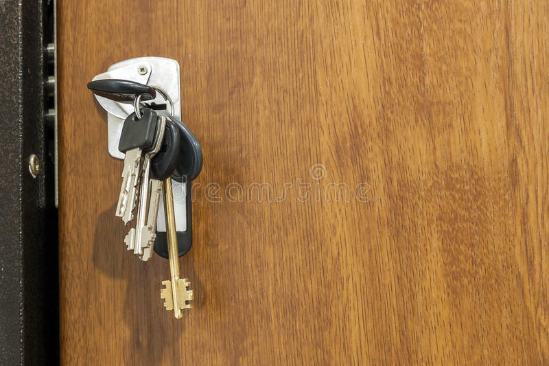 Close-up of bundle of different keys in key hole in wooden texture dood. royalty free stock image