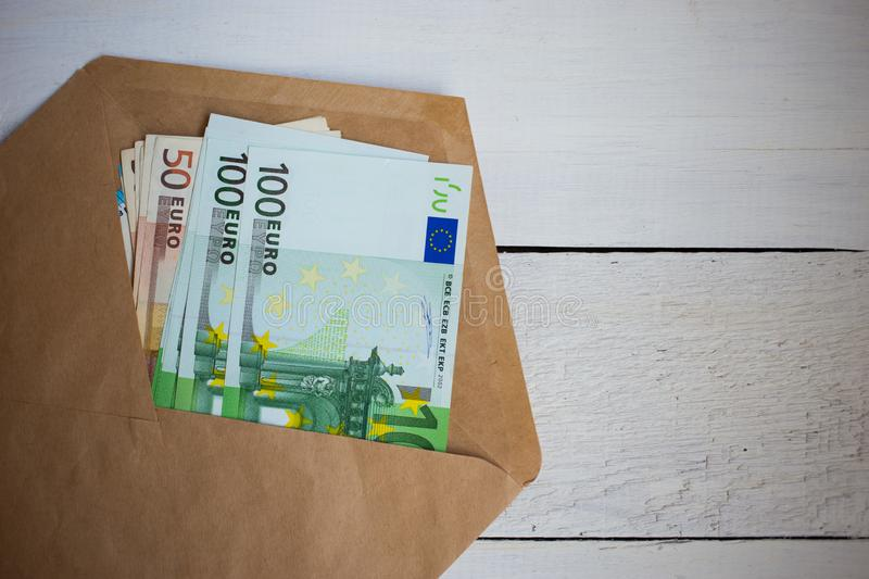 close up bundle of money Euros banknotes in envelope on wooden table stock photo