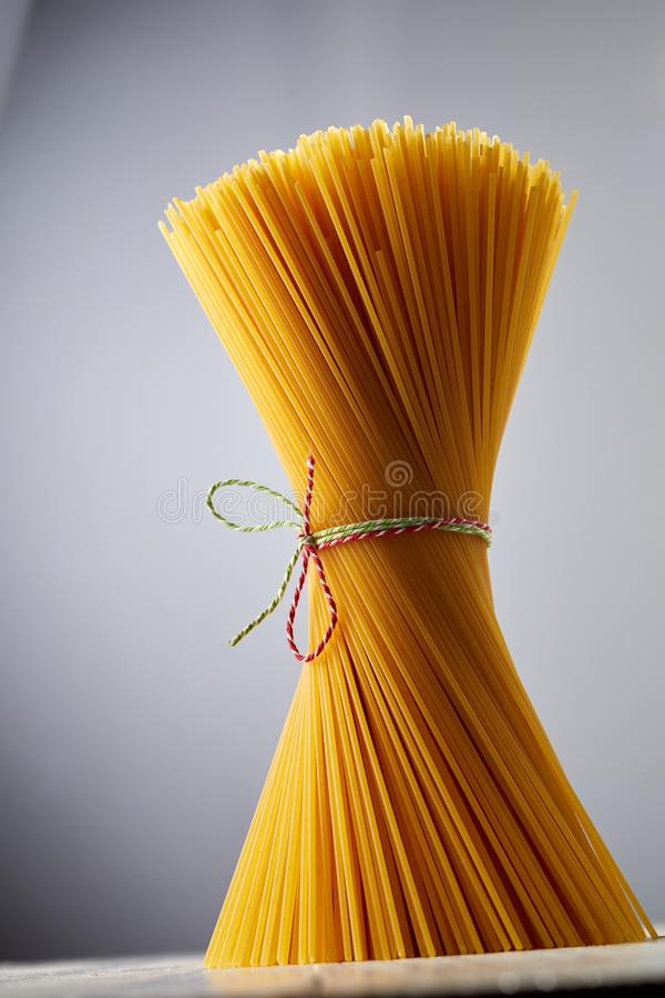 Close up of bundled, uncooked semolina spaghetti stock image