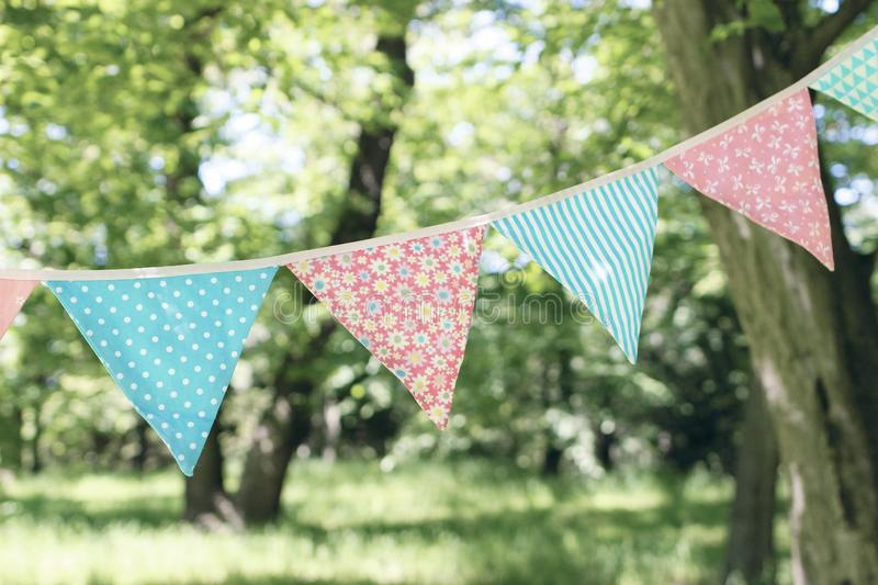 Close up of bunting flags hanging among trees. Summer garden party. Outdoor birthday, wedding decoration. Midsummer. Festa junina concept. Selective focus stock images