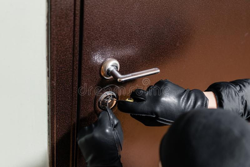 Close up of a burglar with gloves picking a lock. Thief with a passkey. royalty free stock image