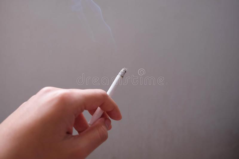 Close up of burning cigarette in hand, Smoking cigarette. Healthy concept. Close up of burning cigarette in hand, Smoking cigarette stock images