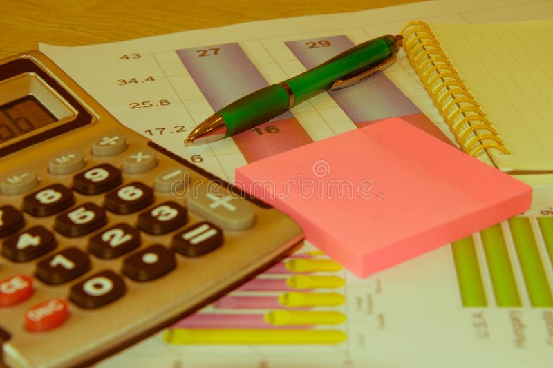 Close up business concept, Calculator, notebook, pen on financial report on table office stock photo