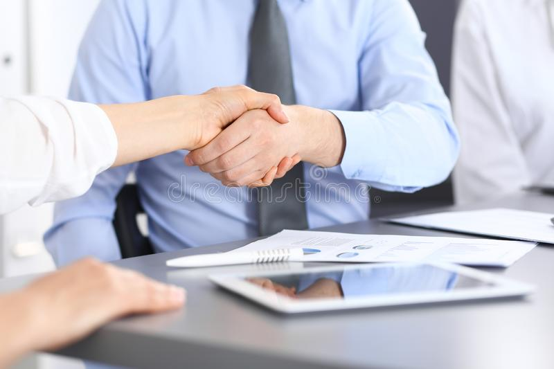 Close-up of business handshake at meeting or negotiation above the desk in office. Partners shaking hands while royalty free stock images