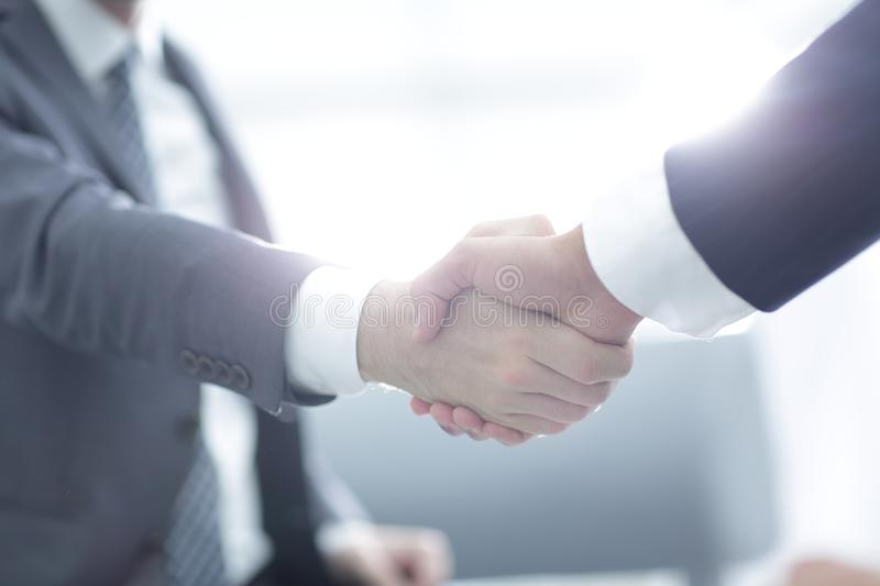 Close up of business handshake in the office. Two confident business man shaking hands during a meeting in the office, success, dealing, greeting and partner stock photography