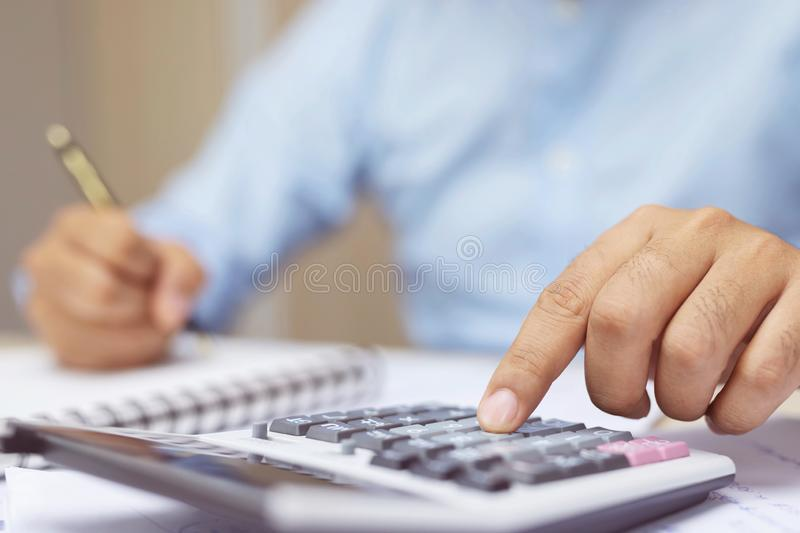 Close up business man hand is writing in a notebook and using calculator counting making notes Accounting at doing finance at home royalty free stock photo