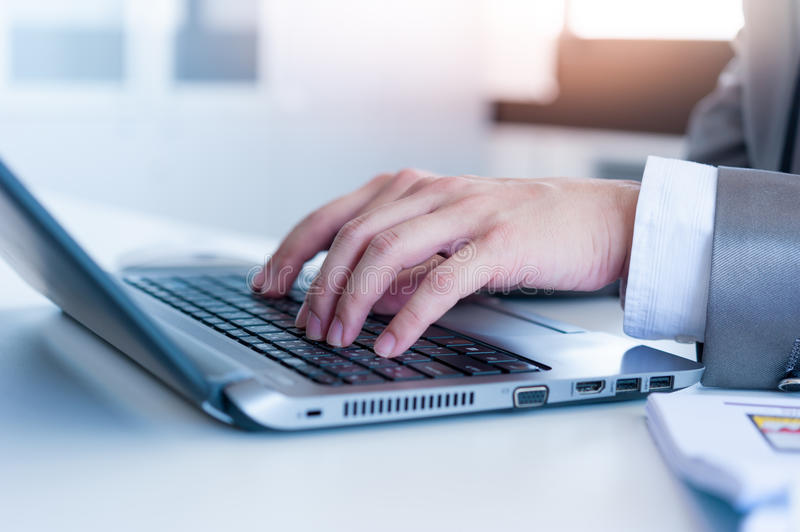 Close up of business man hands typing on laptop computer royalty free stock photography