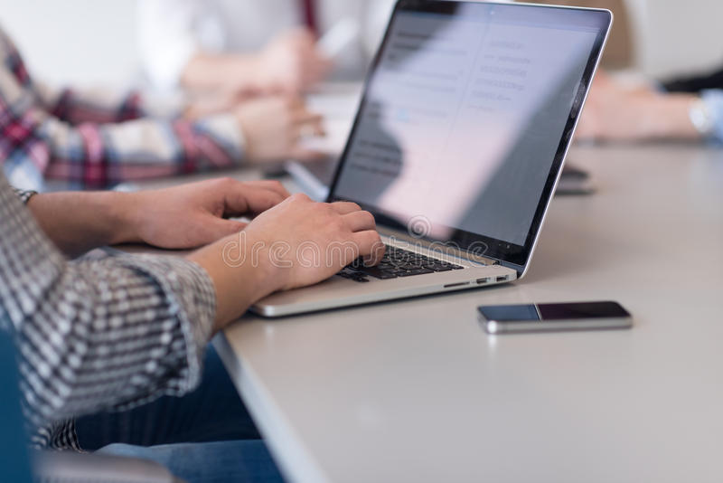 close up of business man hands typing on laptop with team on meeting in background royalty free stock image