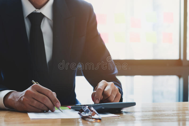Close up, business man or lawyer accountant working on accounts. Using a calculator and writing on documents stock photography