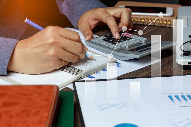 Close up business man working about calculate accounting & finances. Reference form graph document with calculator on modern brown office desk.Double exposure stock photos