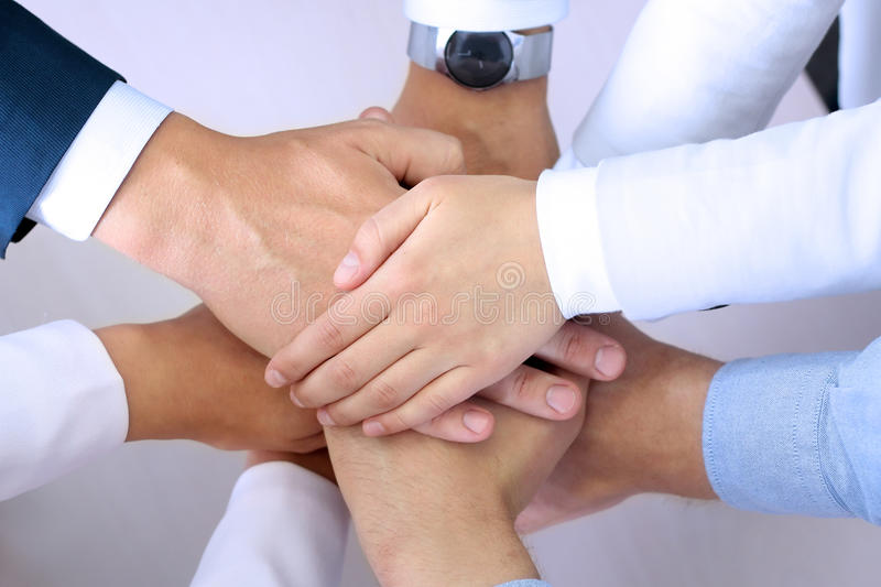 Close-up of business partners making pile of hands at meeting stock photo
