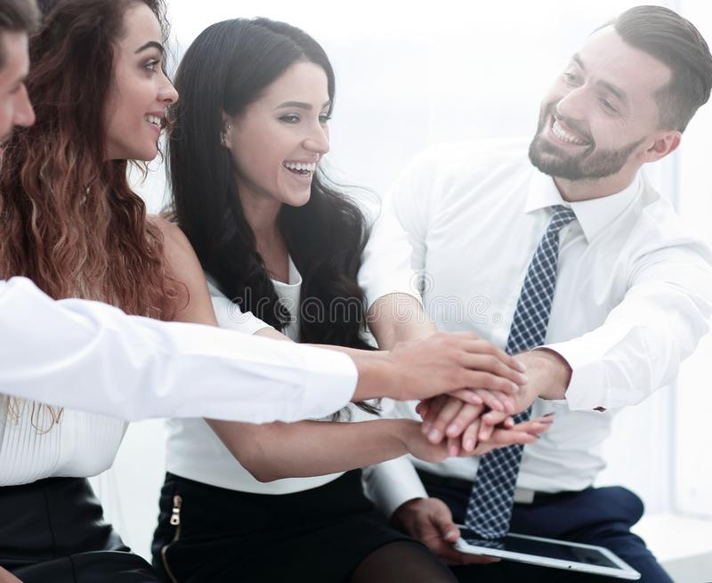 Close-up of business partners making pile of hands stock photo