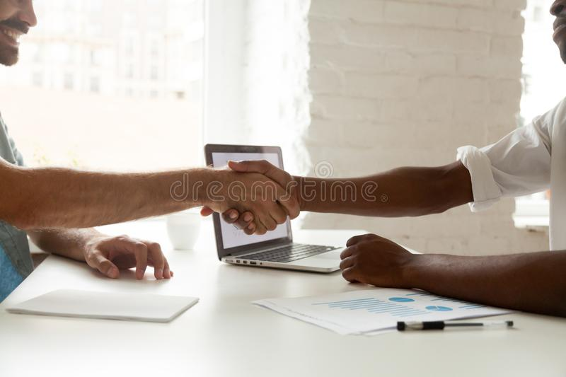 Close up of business partners shaking hands after making agreeme. Close up of business partners shaking hands closing successful financial deal, finishing royalty free stock image