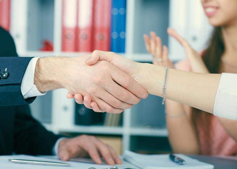 Close up business people handshake on team meeting with clapping group of people blured in background at modern startup royalty free stock photos