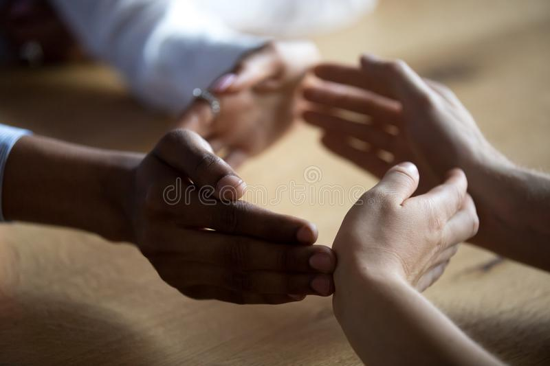 Close up business people join hands forming circle, show unity stock photo