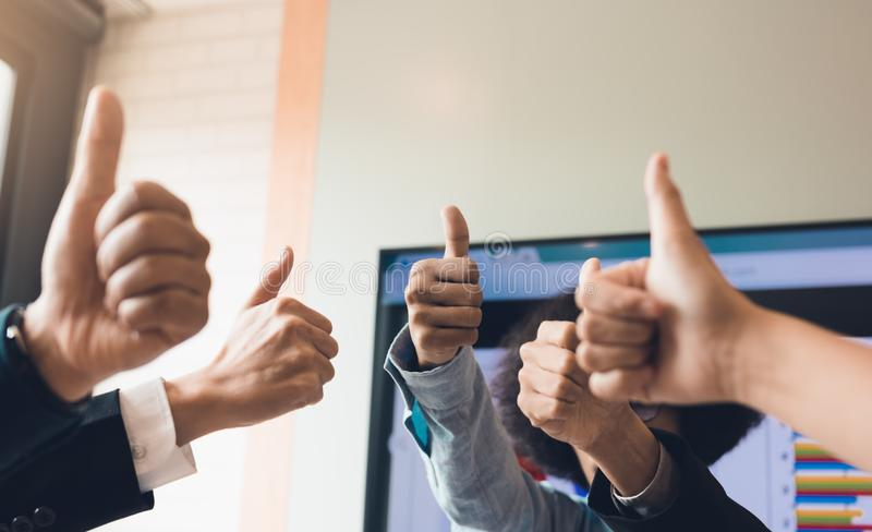 Close up business people pulling thumbs up in office room. stock image