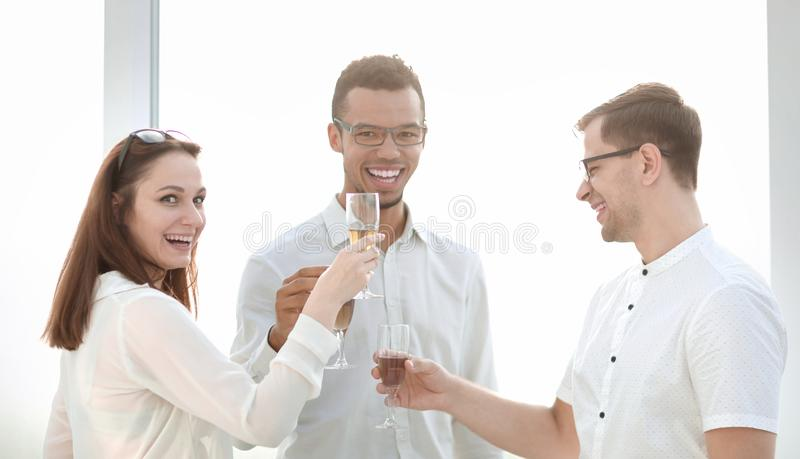 Close up.business team clinking glasses of wine. The concept of a successful startup stock photos