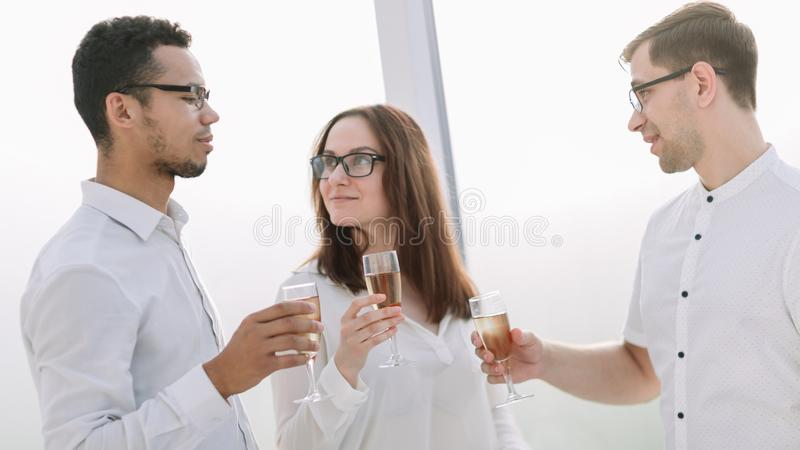 Close up.business team holding a glass of wine. Concept of success royalty free stock image
