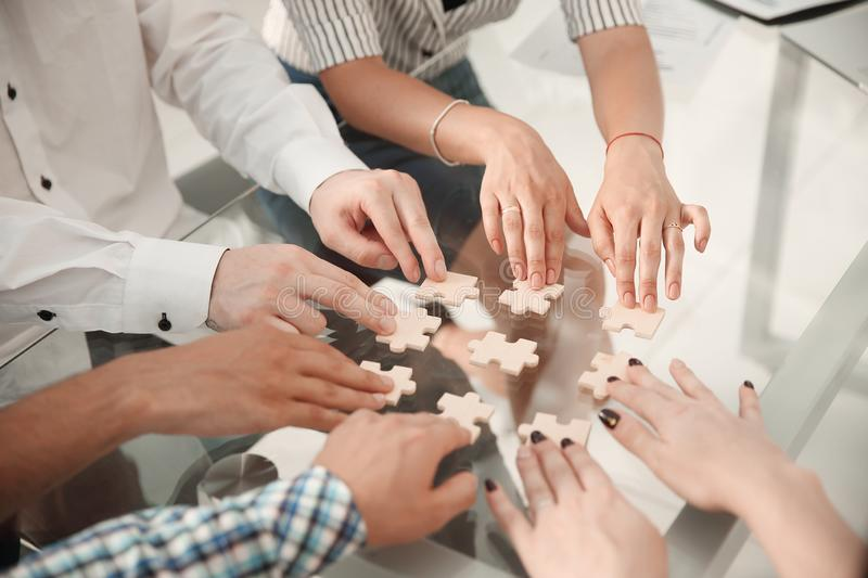Close up. business team sitting at the table and collecting puzzle royalty free stock images