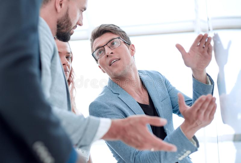 Close up.business team talking, standing near the flipchart royalty free stock image