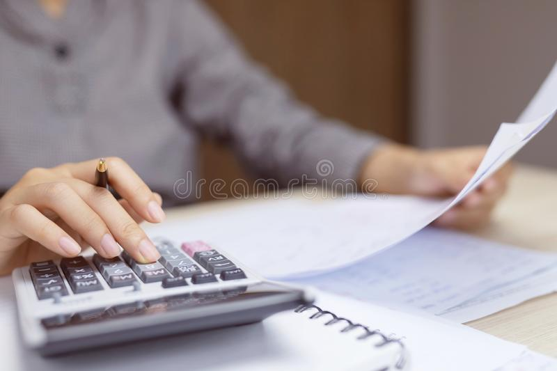 Close up young woman hand using calculator counting making Calculate the cost of checking documents income and tax notes accountin stock image