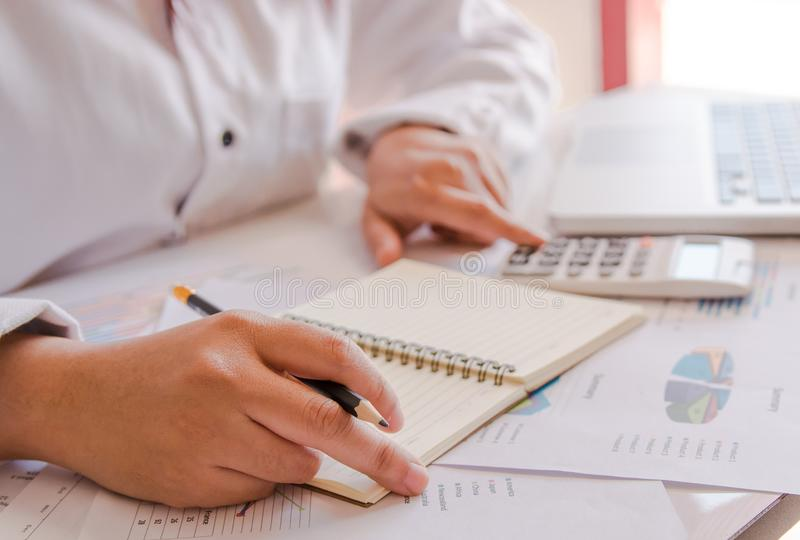 Close up business woman hand using calculator and laptop doing counting making at home stock photography
