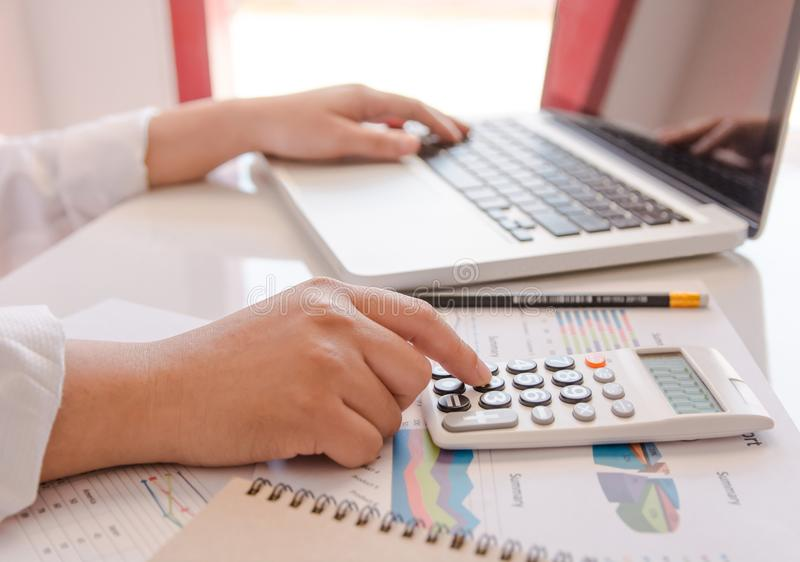 Close up business woman hand using calculator and laptop doing counting making at home royalty free stock photos