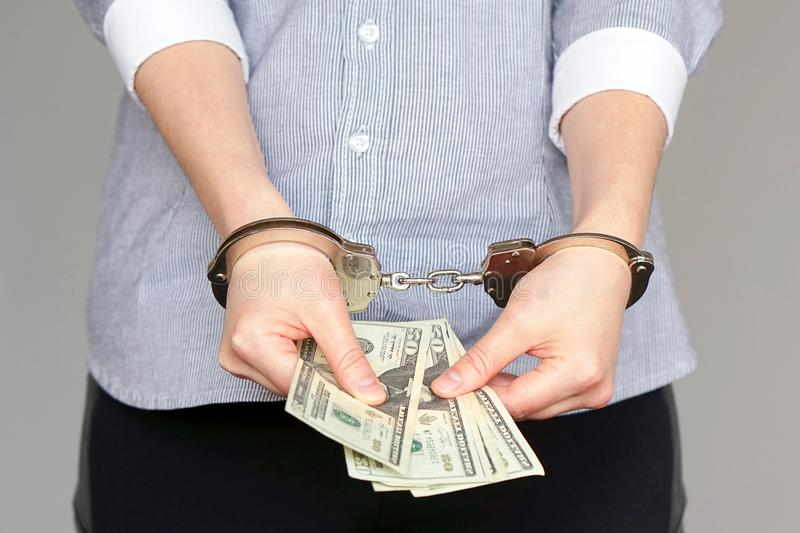 Business women in handcuffs with a bribe stock photos